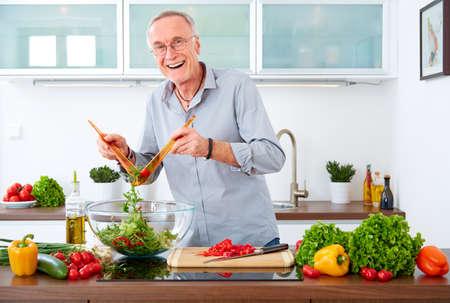 台所で中年の男性がサラダを準備します。 写真素材