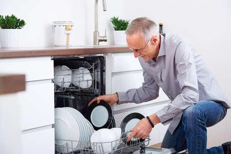 Lterer Mann, der in der Küche, entleeren Sie den Geschirrspüler Standard-Bild - 46632955