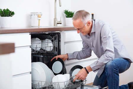 Senior man in the kitchen, empty out the dishwasher