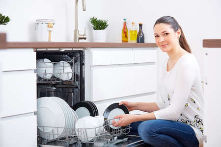 20s: 20s woman in kitchen, empty out the full dishwasher