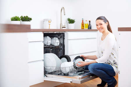20s: Smiling 20s woman in kitchen, empty out the full dishwasher Stock Photo