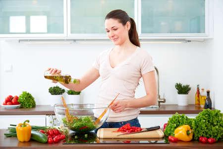 若い女性は、オリーブ オイルとサラダを準備します。