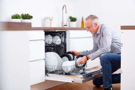 Lterer Mann, der in der Küche, entleeren Sie den Geschirrspüler Standard-Bild - 46632964