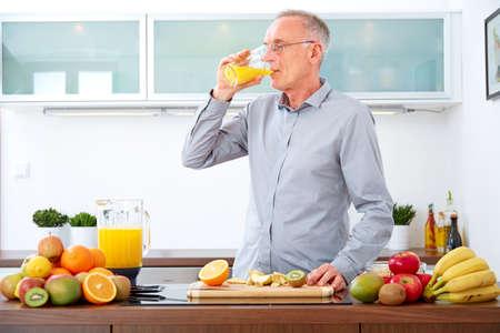 tomando jugo: Hombre maduro que bebe el zumo de naranja recién exprimido en la cocina