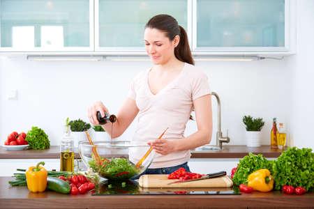 prepare: Young woman in the kitchen prepare salad. Stock Photo