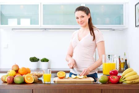 キッチンで若い女性は、朝食に果物を準備します。