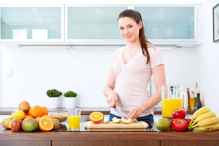 Young woman in the kitchen, prepare fruits for breakfast. Standard-Bild