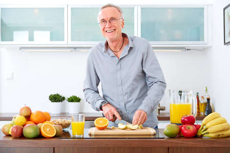 happy senior: Mature man in the kitchen prepare fruits for breakfast. Stock Photo