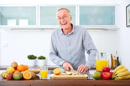 tomando jugo: Hombre maduro en la cocina a preparar las frutas para el desayuno. Foto de archivo
