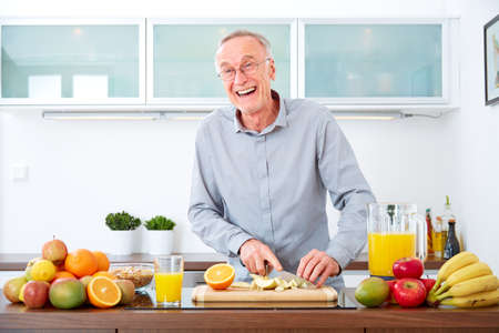 freshly: Mature man in the kitchen prepare fruits for breakfast. Stock Photo