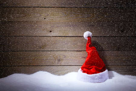 christmas atmosphere: Santa hat in snow on wooden background with snowfall. Stock Photo