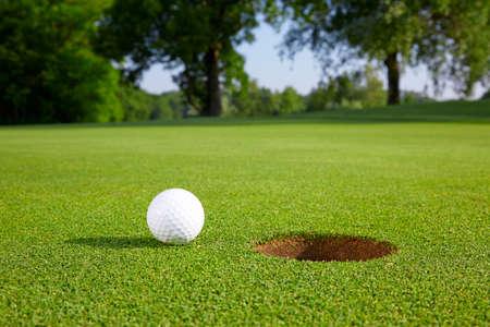穴の近くに緑のゴルフ ・ ボール 写真素材
