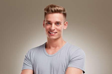 cabello rubio: Retrato de hombre joven sonriente sobre fondo gris Foto de archivo