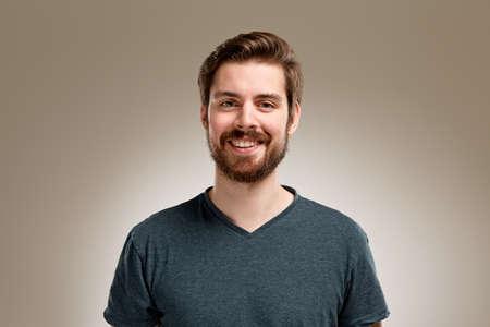 Retrato de la sonrisa del hombre joven con barba, sobre fondo neutro