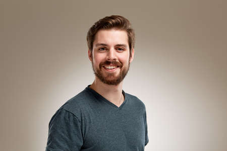 笑顔のひげ、中立的な背景を持つ若者の肖像