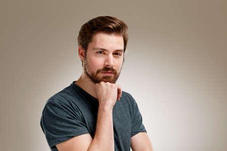 Portrait des jungen Mannes mit Bart, der Hand am Kinn Standard-Bild - 49349082