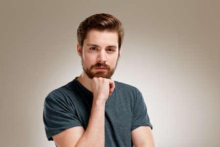 Portrait des jungen Mannes mit Bart, der Hand am Kinn Standard-Bild - 49349083
