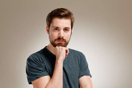 cogitate: Portrait of young man with beard, hand on chin