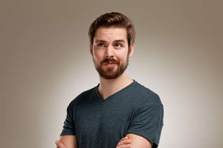 Portrait of young man with beard, think over something funny Standard-Bild