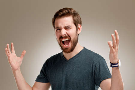 geste: Portrait of screaming young man with beard, on neutral background Stock Photo