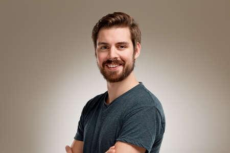 組んだ腕にひげと魅力的な笑顔の若い男の肖像 写真素材