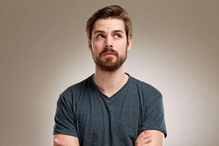 Retrato de hombre joven con barba, mirando hacia arriba a la derecha Foto de archivo