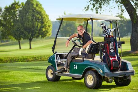 緑の golfcart に座っている中年の男性