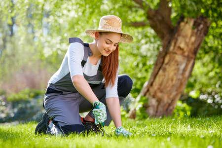 麦わら帽子の庭仕事を持つ若い女性 写真素材