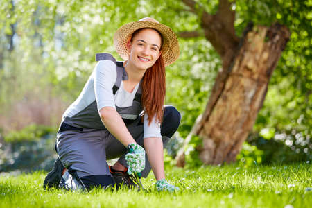 dungarees: Young woman with straw hat working in the garden Stock Photo