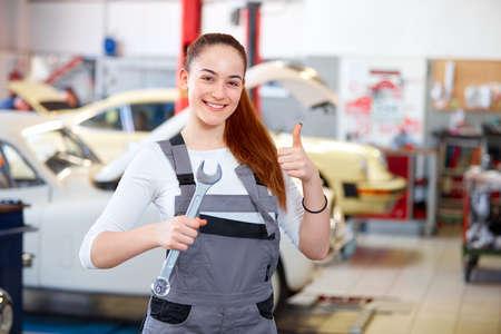 Vrouwelijke monteur in autoservice centrum met moersleutel Stockfoto