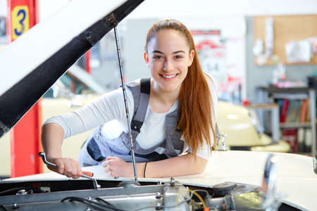 dungarees: Young female mechanic working on car engine with wrench
