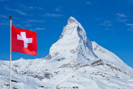 Famous Matterhorn with flag of switzerland on blue sky