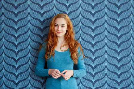 Young smart woman in front of a blue wallpaper
