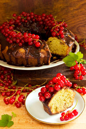 homemade cake: Sponge cake garnished with hot chocolate and redcurrants on a wooden background Stock Photo
