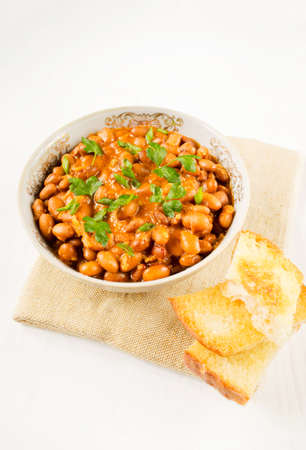 stewed: Stewed beans with toasts on a table