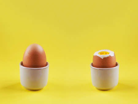fragility: Composition with two boiled eggs on a yellow background