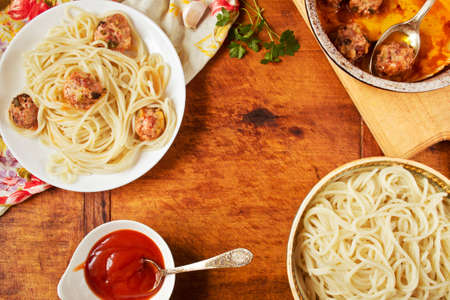 recipe background: Spaghetti with meatballs in a plate on rustic wooden board with fresh parsley and ketchup