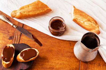 ganache: Breakfast with freshly baked French baguette, hot coffee and chocolate ganache on wooden table