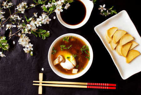 hashi: Asian miso soup with egg, tofu, mushrooms and seaweed, daikon slices and soy sauce on the black table with flowering branches, top view