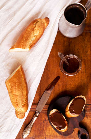 ganache: Breakfast appetizer with freshly baked French baguette, coffee and chocolate ganache on a table Stock Photo