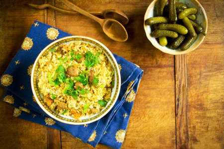 cuisines: Traditional pilaf and pickled cucumber on a wooden table Stock Photo