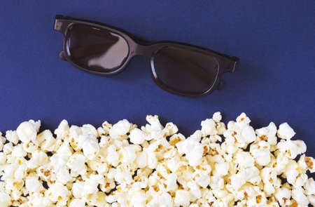 Popcorn and 3d glasses on blue background Stock Photo