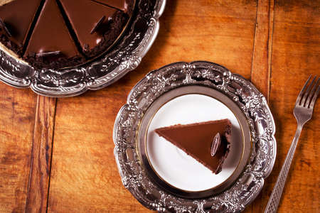 savour: Perfect chocolate cake on wooden table, directly above Stock Photo