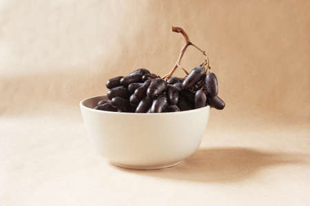 Sweet blue grape in bowl Фото со стока
