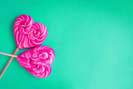 Two heart shaped lollipops on green background with copy space for Valentines Day card Фото со стока