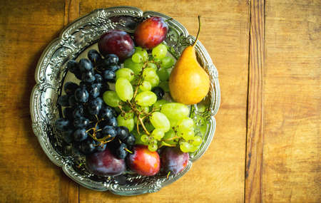 Fresh fruit assortment on a silver tray on a wooden background. Ripe grapes, plums and pear, top view