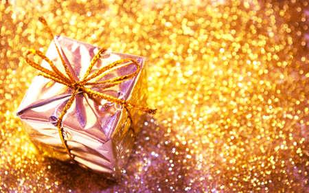 Beautiful gift box on golden glitter background