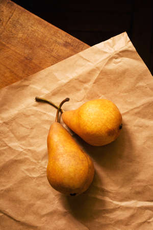 Two ripe sweet pears on paper on the table, top view Фото со стока