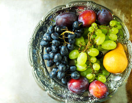 Fresh grapes, plums and pear on a silver tray on a metal background, top view