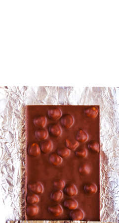 Dark chocolate bar with hazelnuts on a foil isolated on white, top view, vertical image